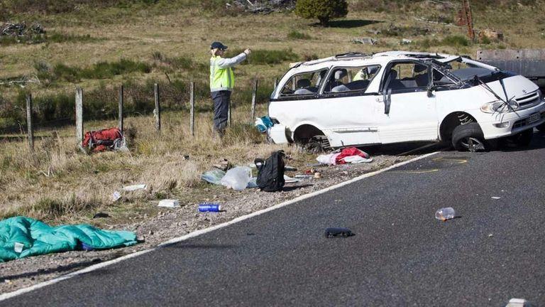 Policemen examine the scene of a minivan crash