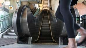 Commuters ride the escalator at the LIRR station