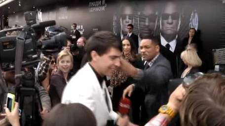 U.S. actor Will Smith, center right, lightly slaps