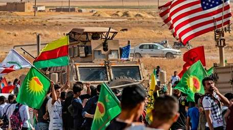 Syrian Kurds protest Sunday near a base for