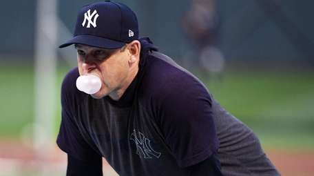 Yankees manager Aaron Boone blows a bubble during