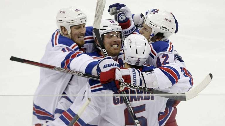 Dan Girardi (5) is congratulated by teammates after