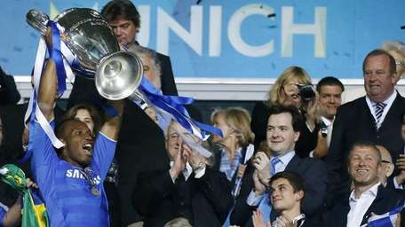 Chelsea's Didier Drogba holds up the trophy at