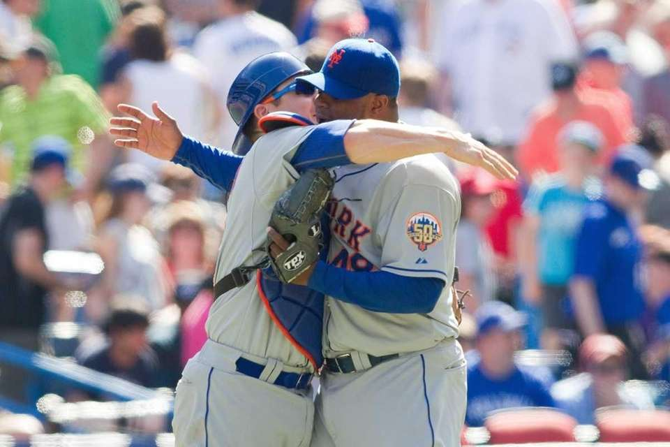 New York Mets catcher Rob Johnson, left, embraces