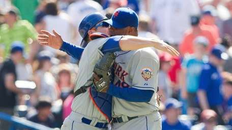 New York Mets catcher Rob Johnson, left, embraces
