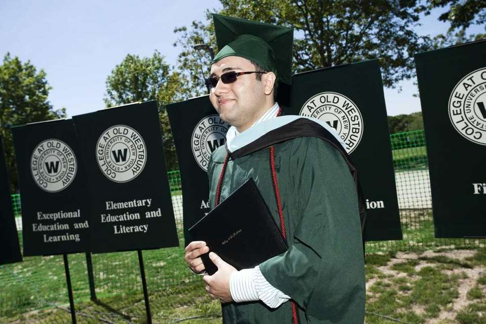 Michael Arroyo, 24, of Farmingdale, receives his master's