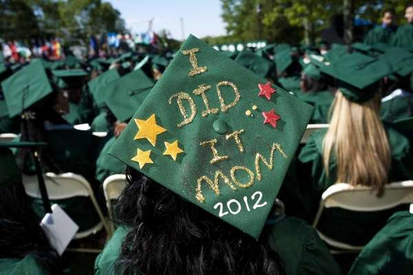 A student wears her graduation cap decorated with