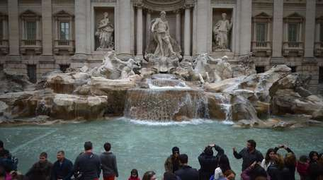 Tourists visit the Trevi Fountain in Rome, Italy.