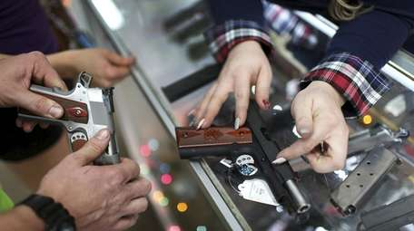 A customer compares handguns before buying one as