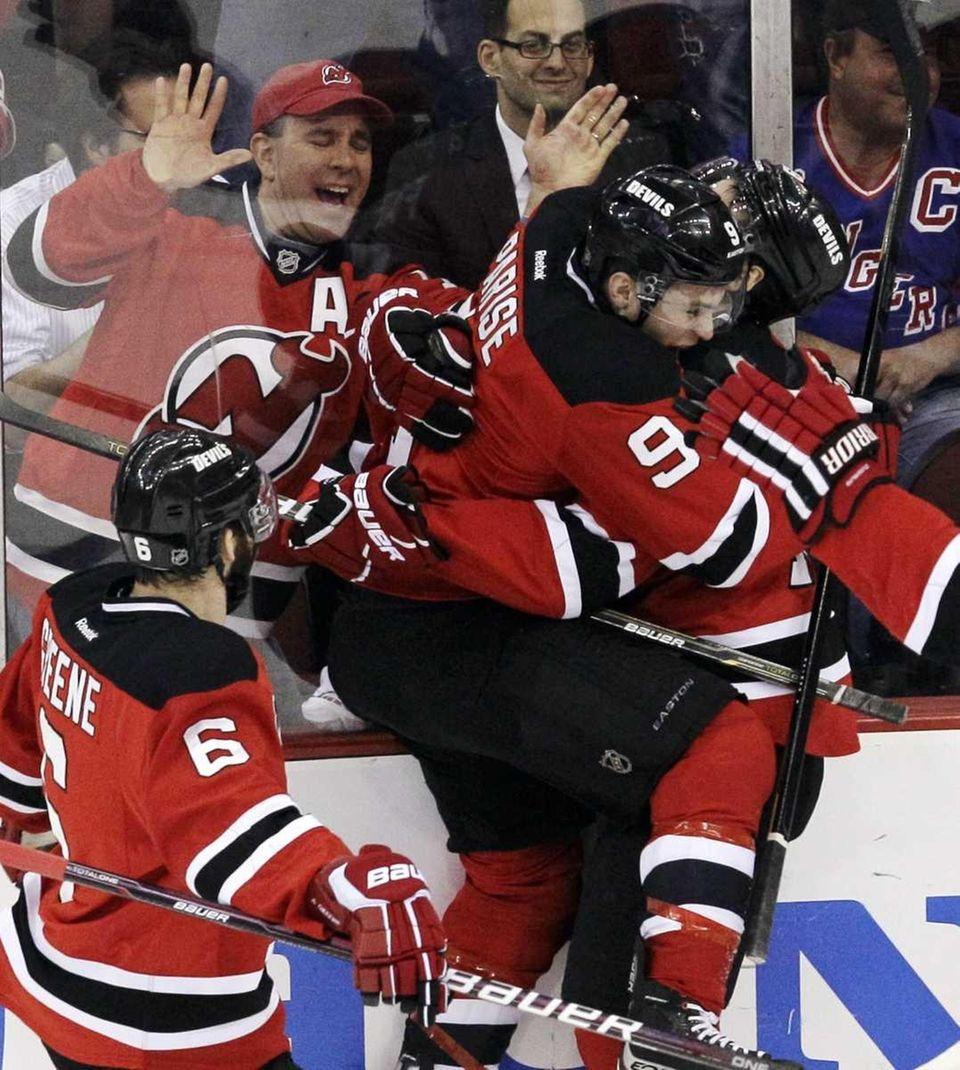 New Jersey Devils' Zach Parise, center, embraces Bryce
