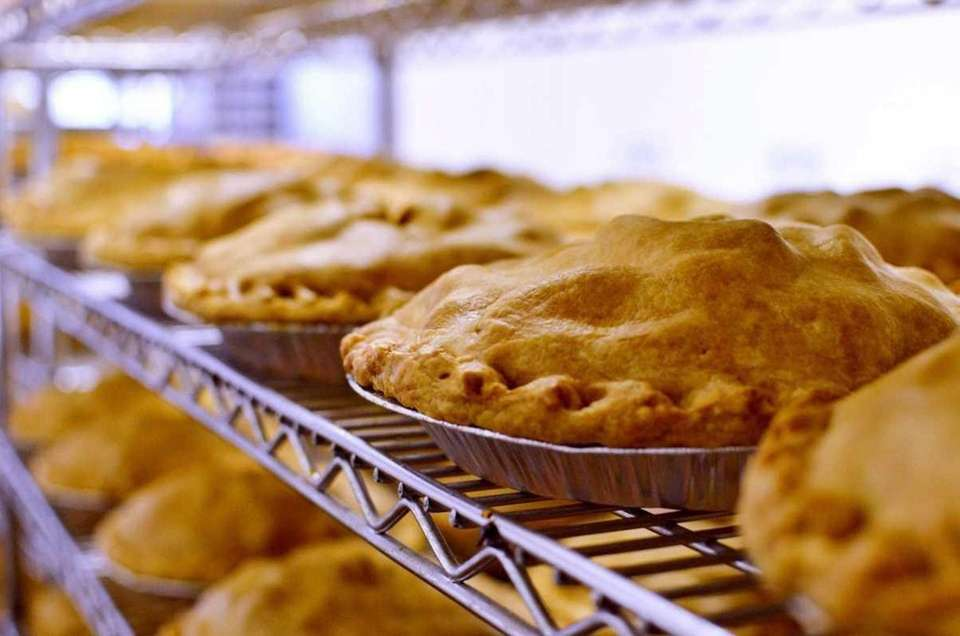 Racks of fresh pies cool after being baked
