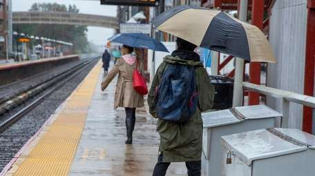 Commuters dodge raindrops at the LIRR station in