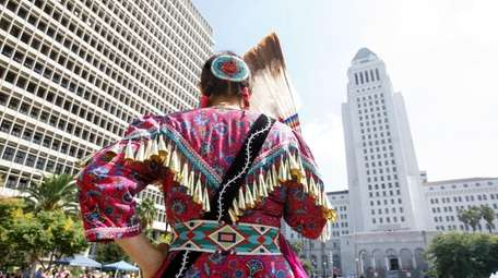 A Native American woman prepares to perform in