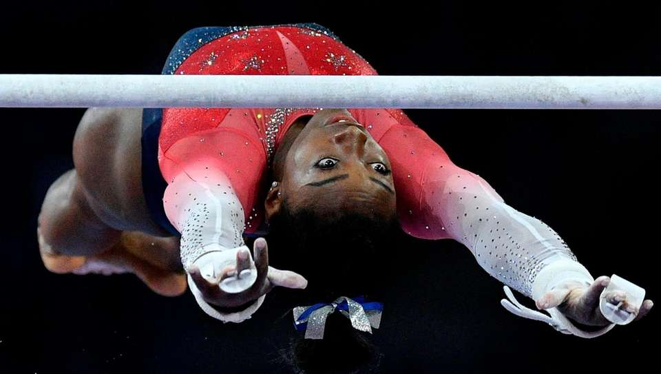 Simone Biles performs on the uneven bars during