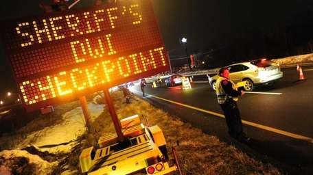 Law enforcement personnel check automobiles for impaired drivers