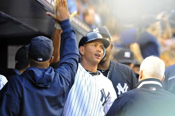 Alex Rodriguez is greeted in the Yankees dugout
