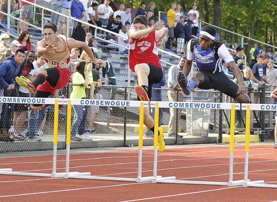 Copiague's Michael Benson, right, clears the last hurdle