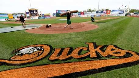 The grounds crew prepares the field before a