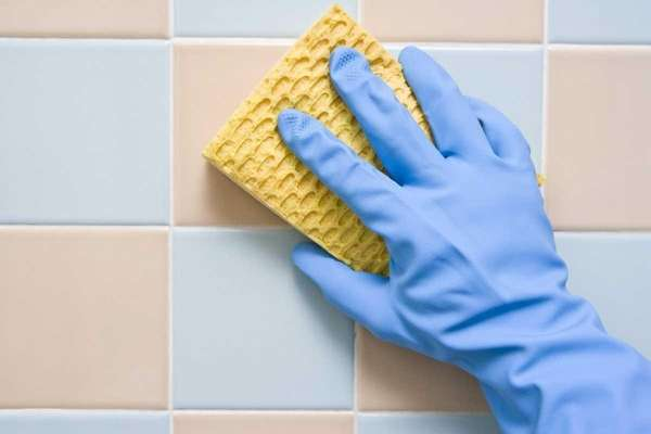 Cleaning the bathroom tiles with a scrubbing pad
