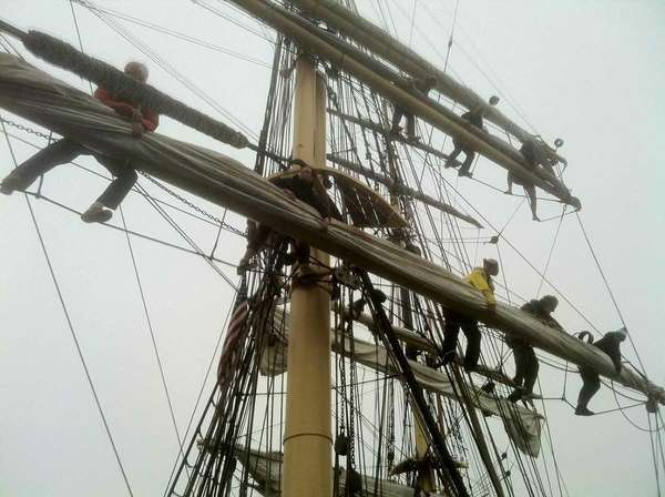 Crew members of the Picton Castle furl the