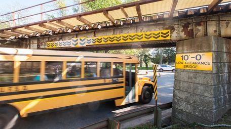 A school bus drives under the LIRR overpass