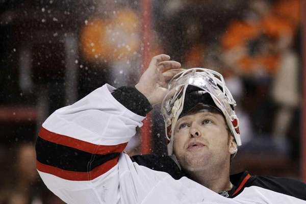 Devils goalie Martin Brodeur blows water into the