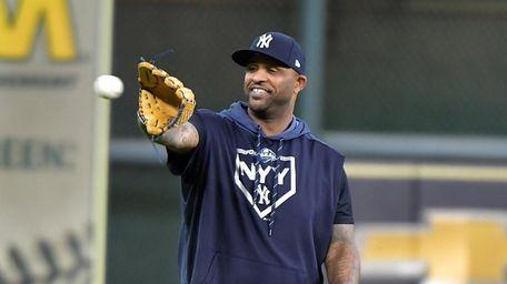 Yankees pitcher CC Sabathia (52) catches a ball