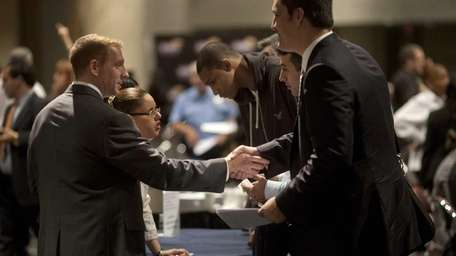 A job seeker shakes hands with a recruiter