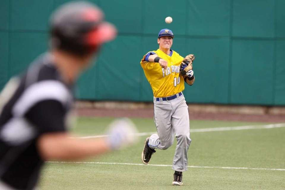 Kellenberg's Doug Kraeger throws to first base for