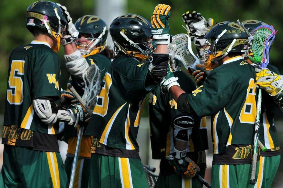 Ward Melville teammates celebrate after a goal extended