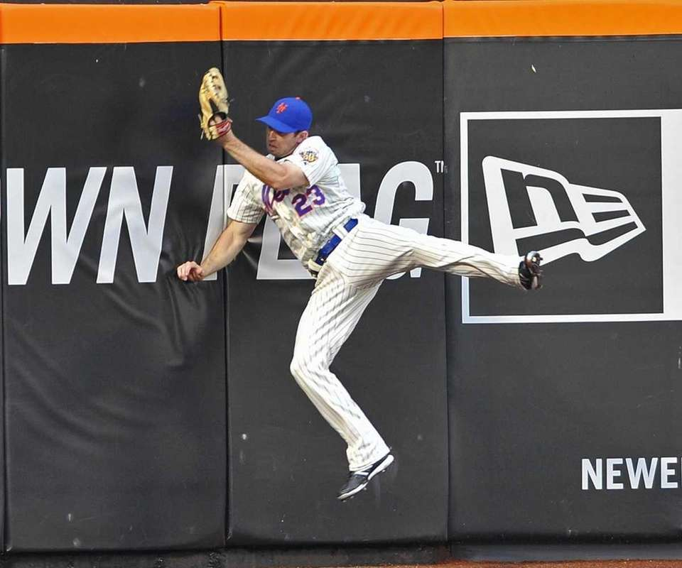 Mets left fielder Mike Baxter crashes into the