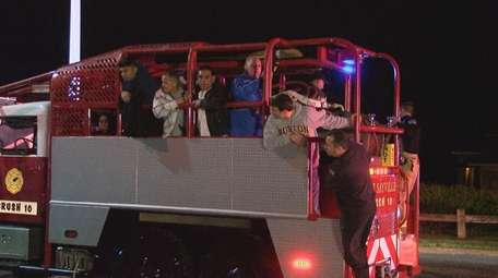 Firefighters help guests leave the wedding reception Friday