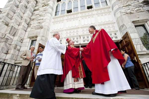 Bishop William Murphy, center, congratulates Msgr. Jeffrey Madley