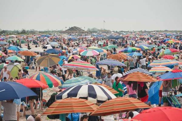 Umbrellas and spectators fill in the sand at
