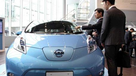 Visitors look at a Nissan Leaf electric car
