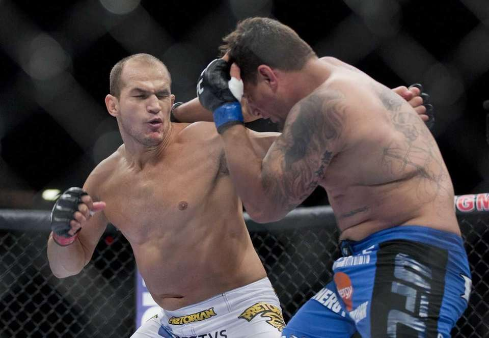 Junior Dos Santos, left, throws punches against Frank