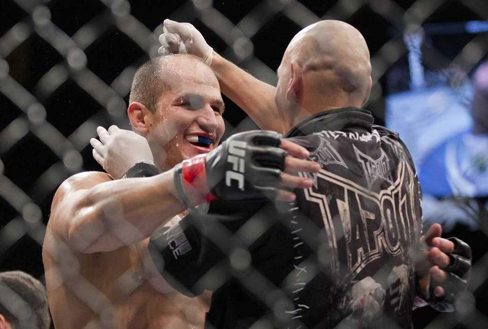 Junior Dos Santos, left, reacts after defeating Frank