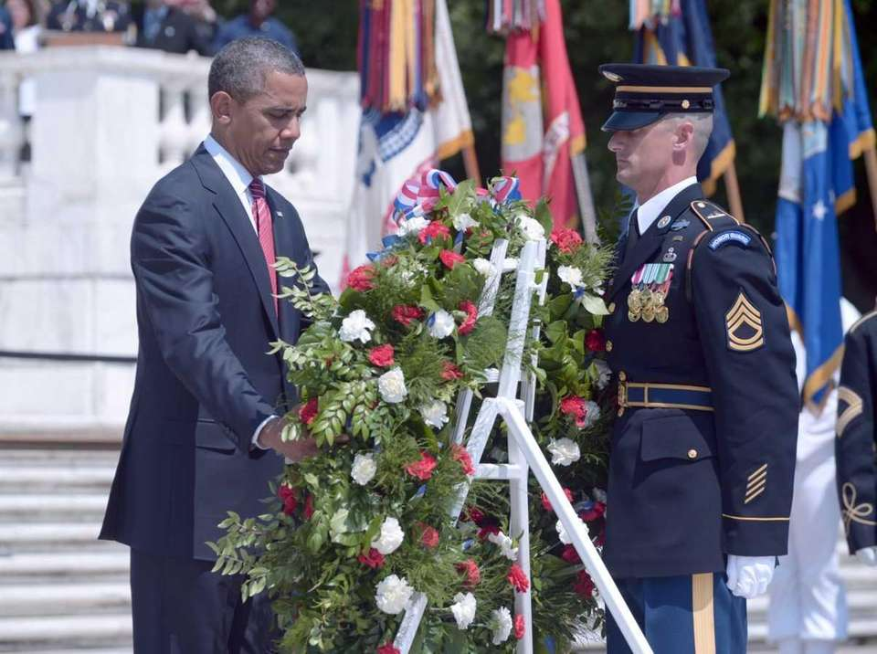 President Barack Obama places a wreath during a