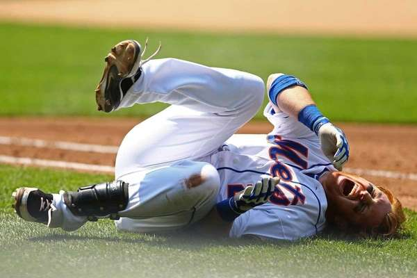 Justin Turner reacts in pain after a fall