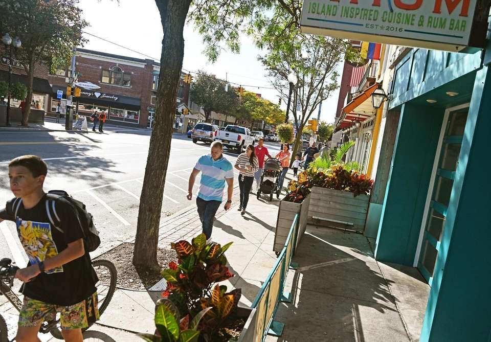 People stroll downtown Patchogue, Saturday, Oct. 12, 2019.