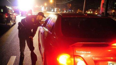 Suffolk County Deputy Sheriff Robert Howard checks cars
