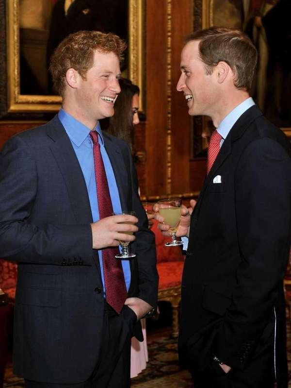 Prince William, right, talks with brother Prince Harry