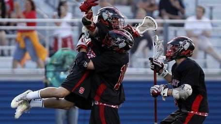 Syosset's Alex Concannon (2) is lifted by teammate
