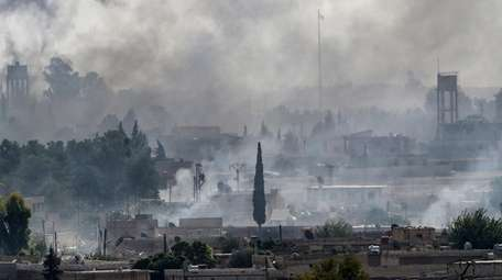 Smoke rises Sunday over the Syrian town of