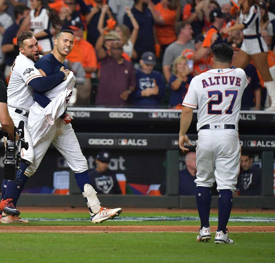 Houston Astros shortstop Carlos Correa (1) is hugged