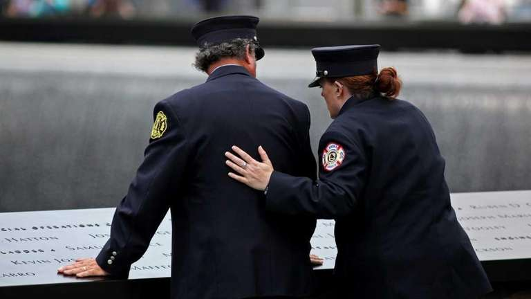 A first responder comforts another as they lean