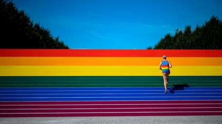 A man walks on steps covered in rainbow