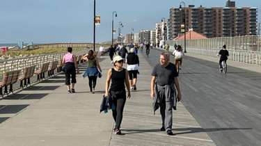People enjoy mild weather on the boardwalk at