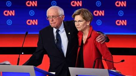 Sens. Bernie Sanders and Elizabeth Warren hug at