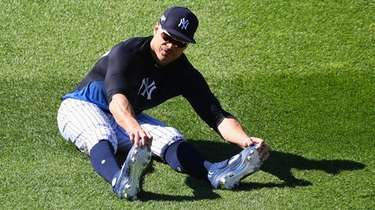 Giancarlo Stanton stretches in the outfield during warmups